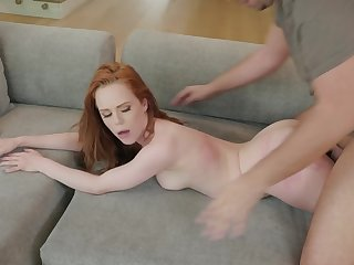 A redhead is getting fucked in her sopping and sexy pussy on the sofa