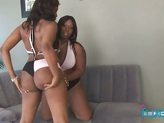 Two big bottomed black lesbians fuck each others cunts with strapon