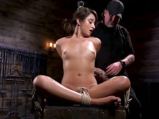 Tied up and suspended porn model Isabella Nice gets her pussy punished in the dark room